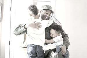 U.S. Military solider hugging his children.