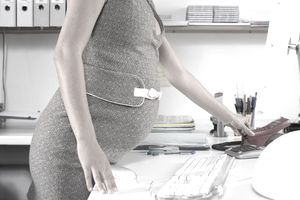 Young pregnant woman picking up phone on desk, mid section, side view