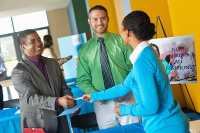 Young professional accepting business card at job fair.