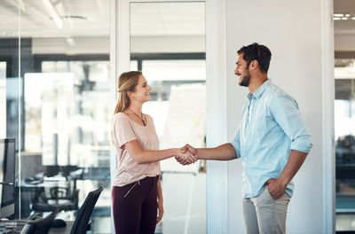 Shot of a businessman and businesswoman shaking hands in a modern office