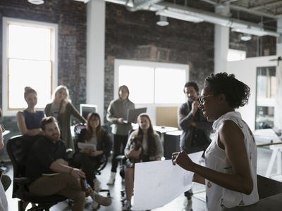 Female architect with blueprint leading meeting in open plan loft office