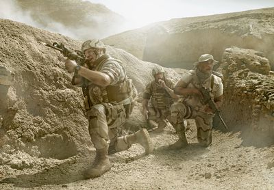 Soldiers advancing in dry rural landscape