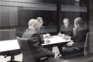 Department managers talking in a glass-walled meeting room.