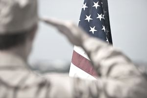 Member of the military saluting flag.