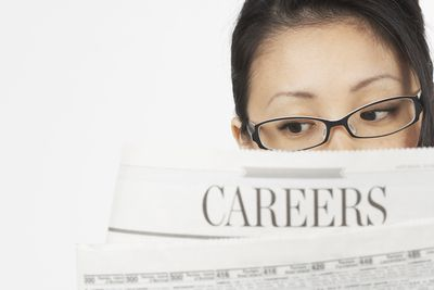 Teenager looking through the employment section of a newspaper