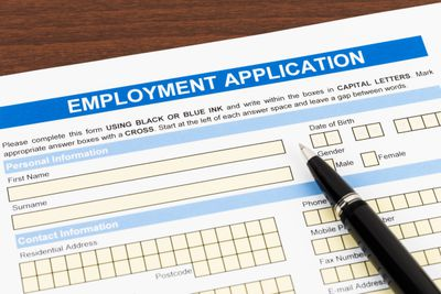 Employment application form with pen; document is mock-up