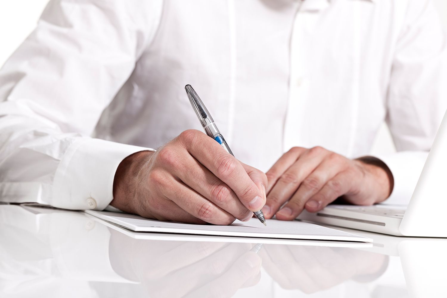 Businessman holding a pen & taking notes on paper.