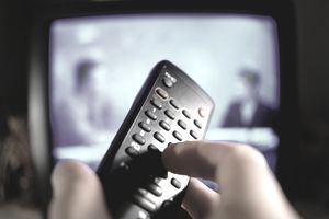 A photo of a hand on a TV remote control with the news on in the background.