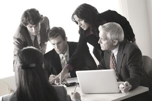 Young business people working together under a lot of pressure in a conference room.