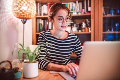 Young woman working on a laptop computer at home
