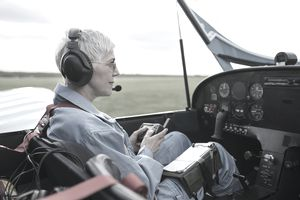 An older woman preparing for a flight in a small aircraft.