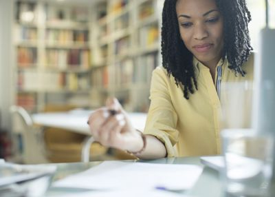 Business woman writing on paper in her office.