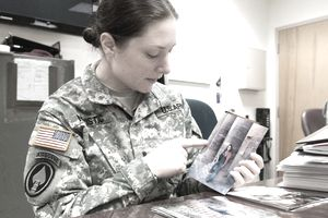 Woman soldier in fatigues at desk pointing at picture