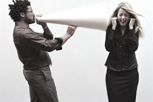 Man with a giant megaphone yelling into a woman's ear