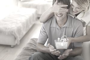 Woman covering a man's eyes and giving a gift