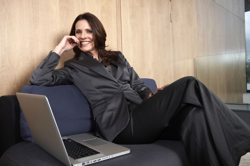 Business woman dressed for a formal work environment is waiting with a computer.