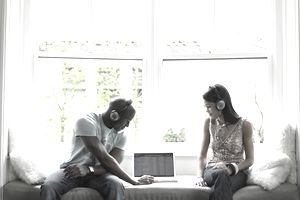 Two young people listening to music on a laptop