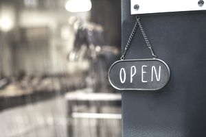 Close up of open sign on glass door to a bakery.