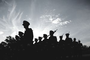 Silhouetted naval cadets marching in formation, low angle view
