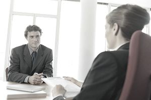 Businesswoman with clipboard talking to businessman across desk