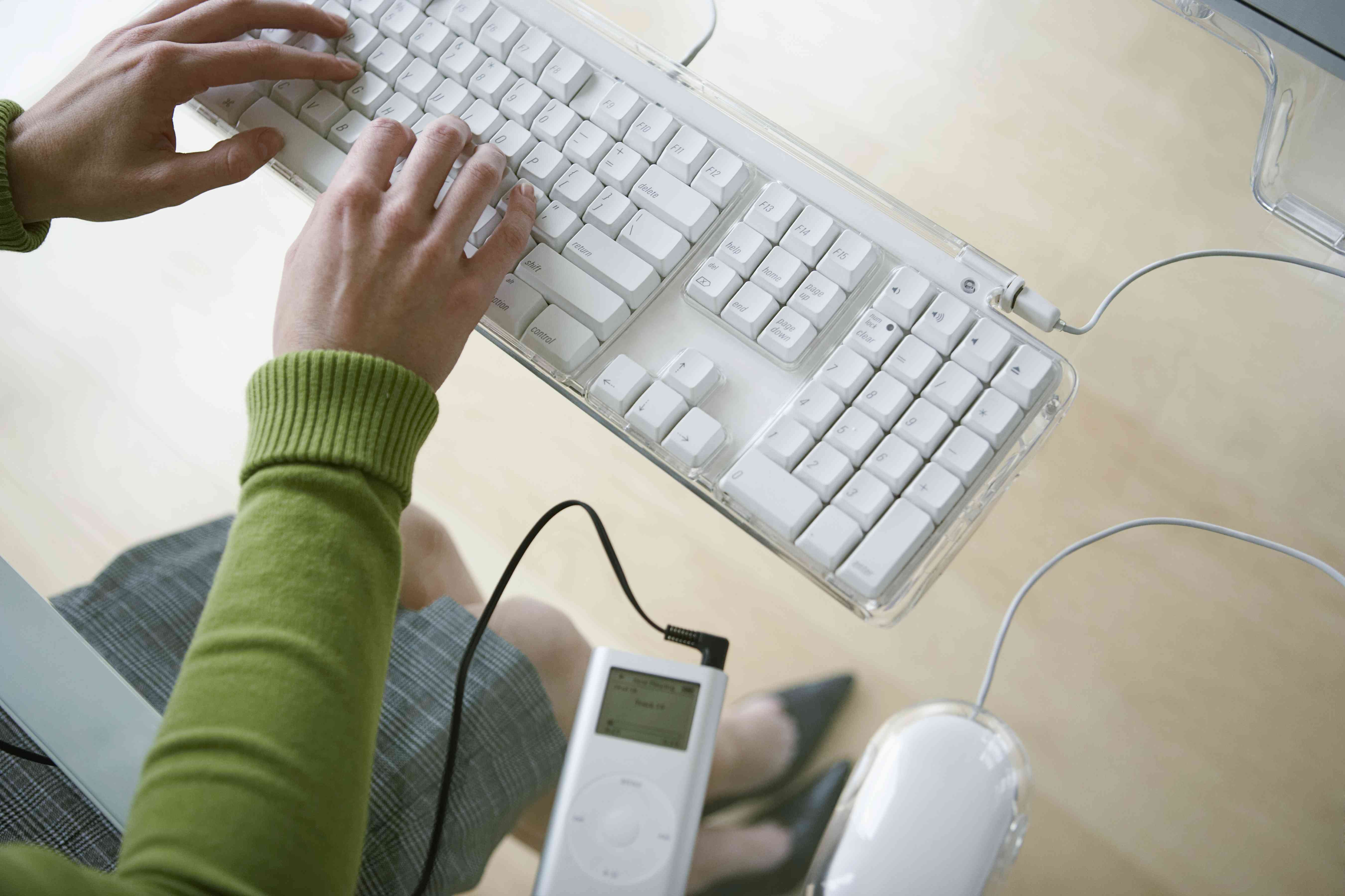 Woman typing on computer keyboard at transparent desk