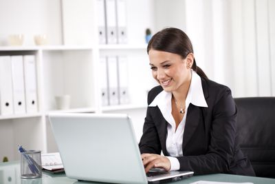 A smiling successful businesswoman reviews and evaluates a resume cover letter on her laptop that she likes.