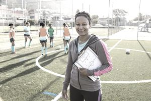Portrait of female coach at soccer team practice