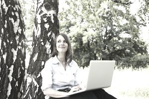 woman sitting against tree with laptop
