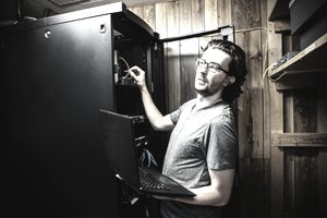 A man stealing data in a small business server room