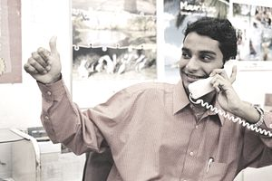 Sales agent on phone making thumbs up sign to confirm appointment