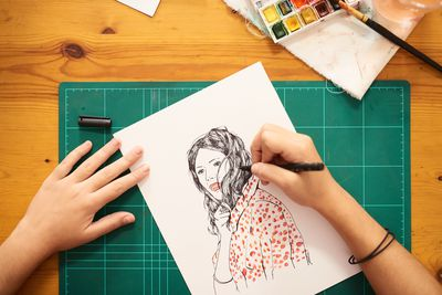 Hands drawing a picture of a women