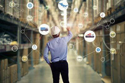 Supply chain and logistics executive looking at a flow chart in a warehouse.