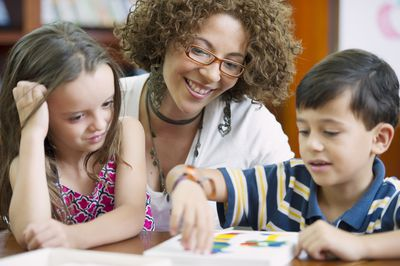 A mom at work as a teacher's assistant, helping two children complete an assignment.