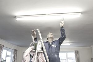 maintenance man fixing overhead light in office
