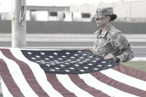 A Soldier on flag detail prepares to fold Old Glory as part of a daily reveille ceremony
