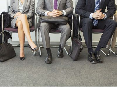 Three interviewees sitting in a row of chairs preparing for a government job interview