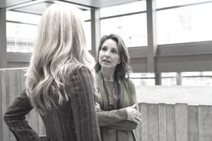 Two female employees participate in healthy conflict about a decision at work.