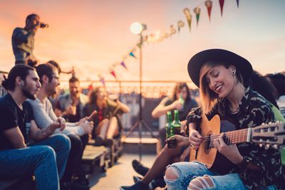 A small musical concert being held on a rooftop at sunset.