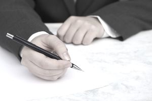 Man in suit writing a letter for an internship in finance.