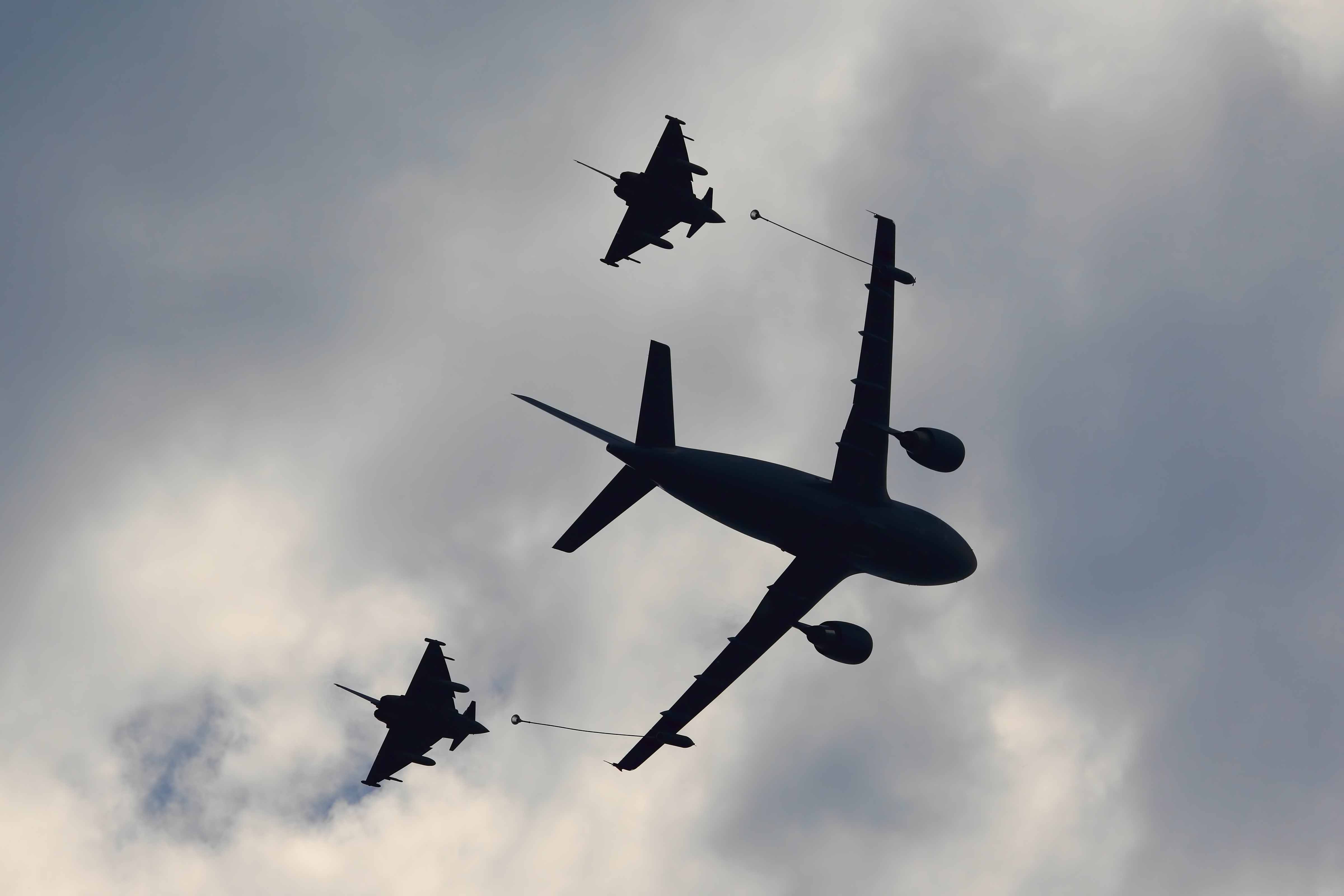 Military flying refueling tanker fueling two fighter jets in a cloudy sky.