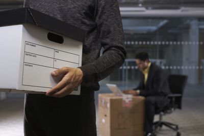 Close-up of Businessman Holding Box, representing wrongful demotion.