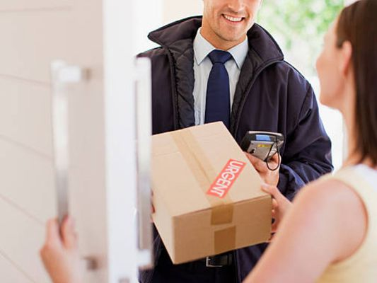 Smiling delivery driver handing woman a package at her front door