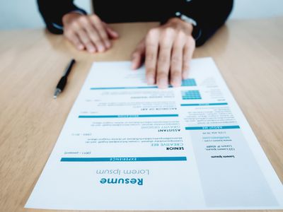Midsection Of Businesswoman With Resume At Table In Office