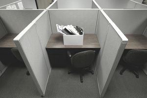 Cubicle with box of personal belongings during layoff