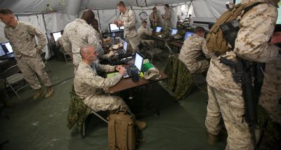 Marine intelligence soldiers working on computers in a tent.