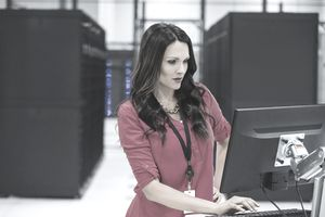 female computer Systems Analyst working on a computer in a server room
