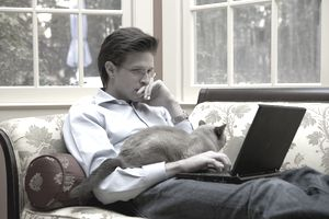 man sitting on sofa with laptop and cat on his lap