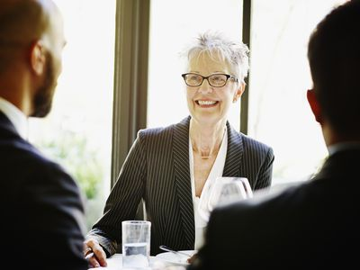 Smiling senior female executive at lunch meeting
