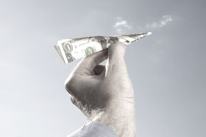 Man holding money airplane.