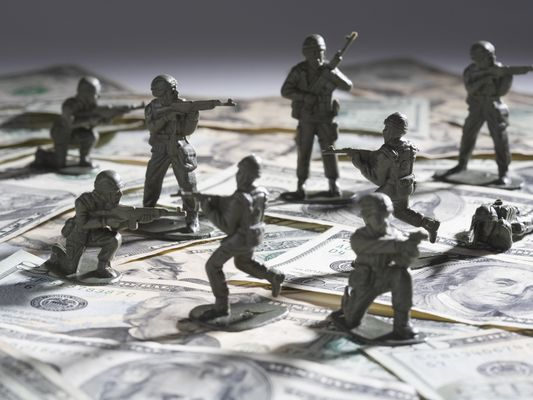 Close-up of plastic solders fighting on top of paper currency depicting military pay